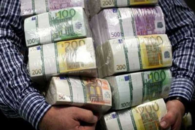 There are 63 people in Montenegro with millions in bank accounts. Man holding bundles of euro bills